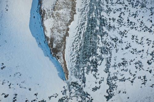 Snowy rock on frozen ocean in winter