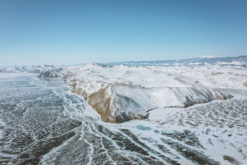 Scenic view of mounts with snow on frozen ocean under cloudy blue sky in wintertime