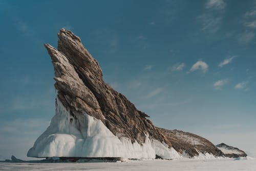 Rock with ice under cloudy sky in wintertime