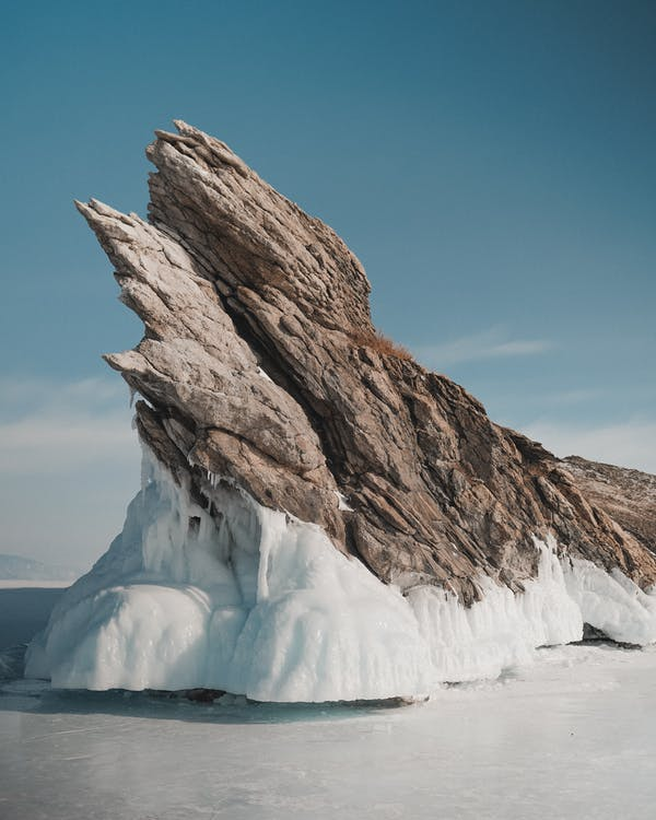 Picturesque view of rugged rocky formation on frozen ocean with horizon under cloudy sky on sunny day