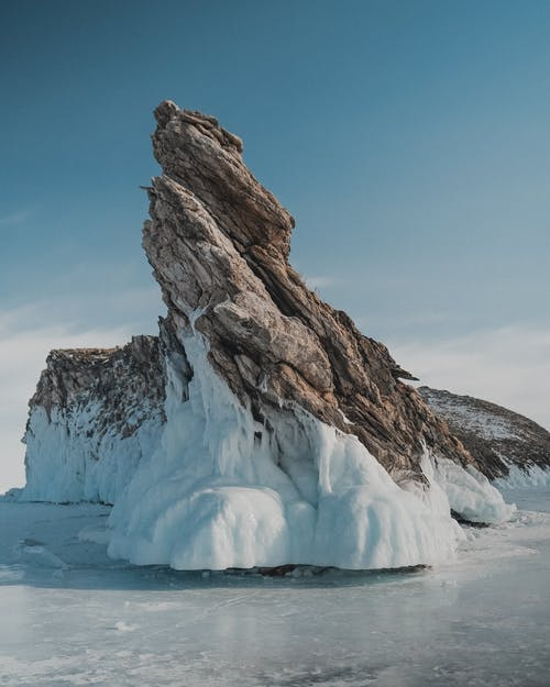 Rock on frozen sea under blue sky in wintertime