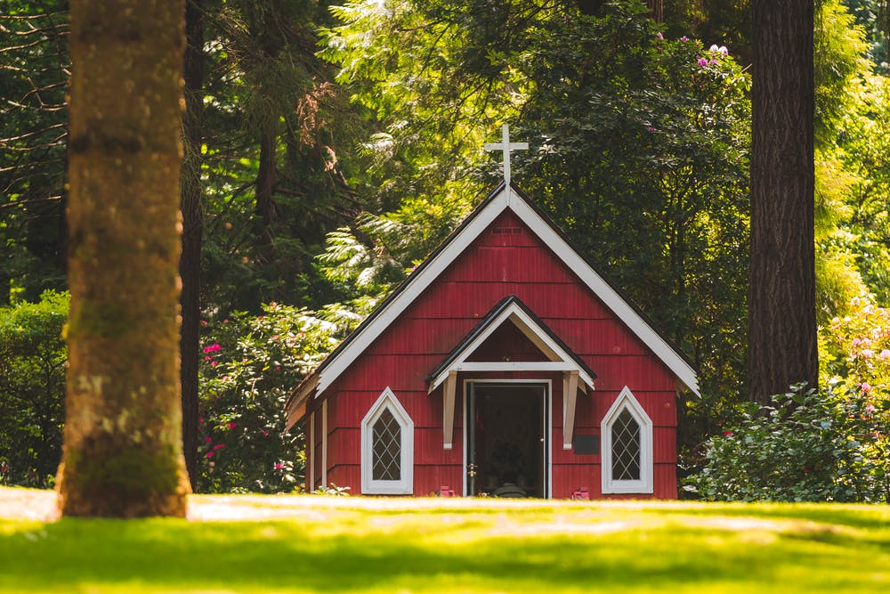 Red chapel on a grassy field with trees. | Photo: Pexels