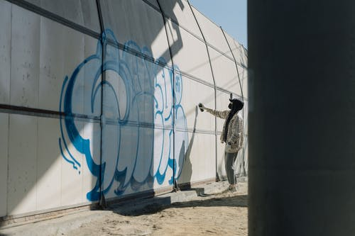 Side View Photo of Person Doing Graffiti on Wall