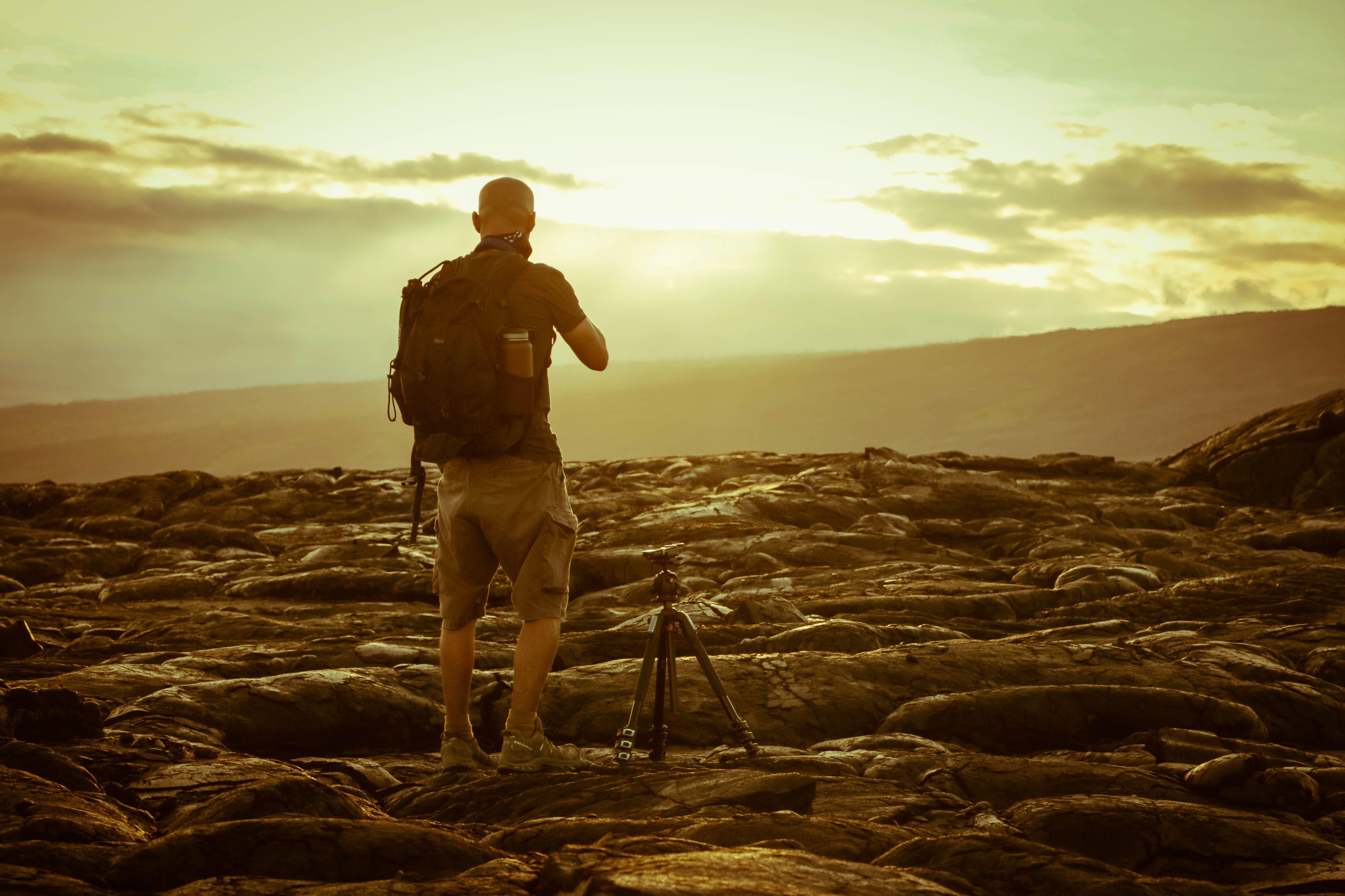 Man Beside Tripod on Rocks during Golden Hour
