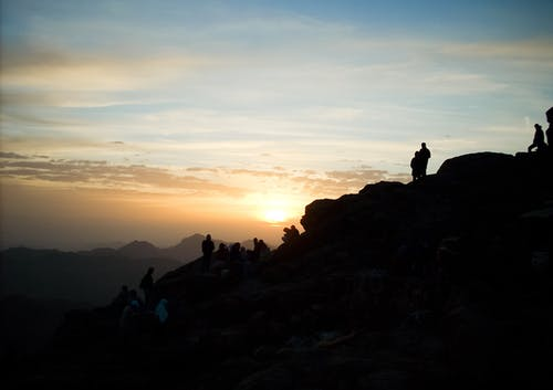 Silhouette of Group of Person Hiking on the Mountain