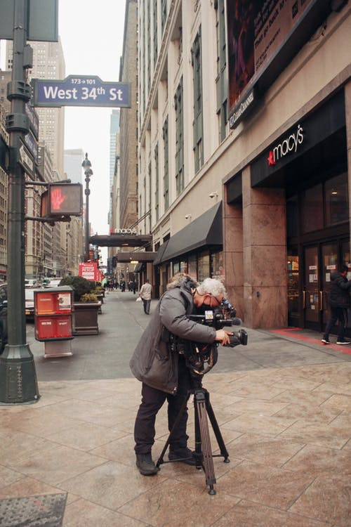 Full body of anonymous aged male installing photo camera on tripod for taking photos of modern building