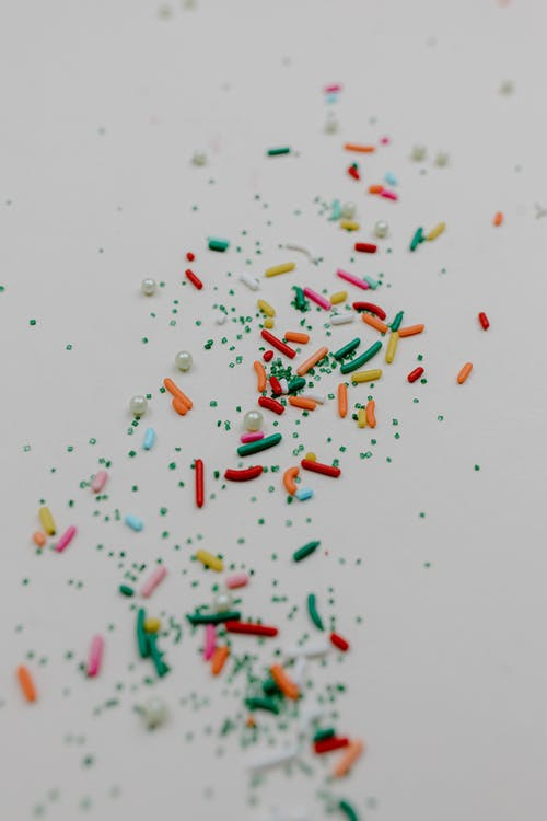 Red Green and White Sprinkles on White Surface