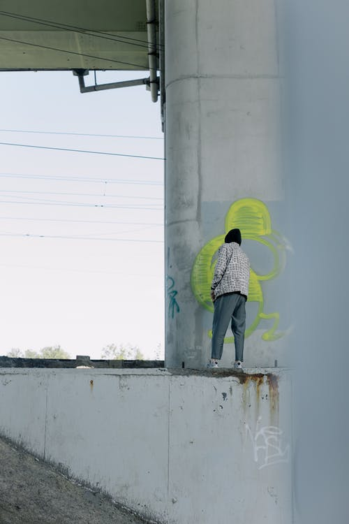 Person in Hoodie Jacket Doing Graffiti on a Wall