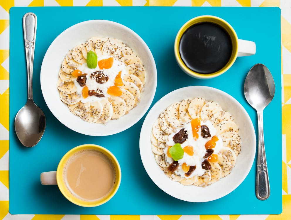 Breakfast for Two Served in Plates with Coffee Cups and Spoons