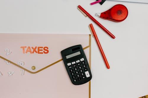 Calculator Beside Red Pens