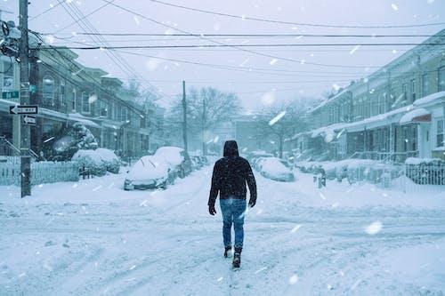 Unrecognizable man walking on snowy street