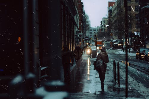 Crowd of people strolling on snowy walkway between road and residential building on street in city during snowfall in winter time