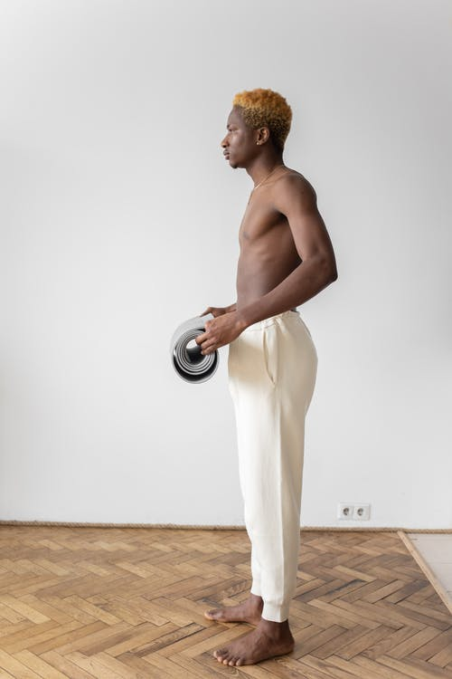 Man in White Pants Holding Gray Yoga Mat