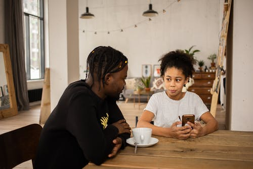 African American man sitting at table with cup of coffee and talking to daughter browsing cellphone