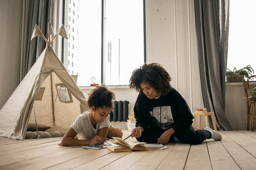 African American woman with Afro hairstyle doing homework with daughter lying on floor in kid bedroom