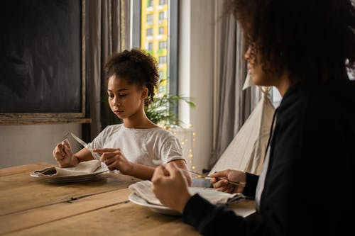 Black girl at table with plate and cutlery near anonymous mother