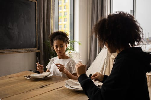 Pensive African American girl sitting at wooden table with plate and cutlery in hands while learning dining etiquette with anonymous mother
