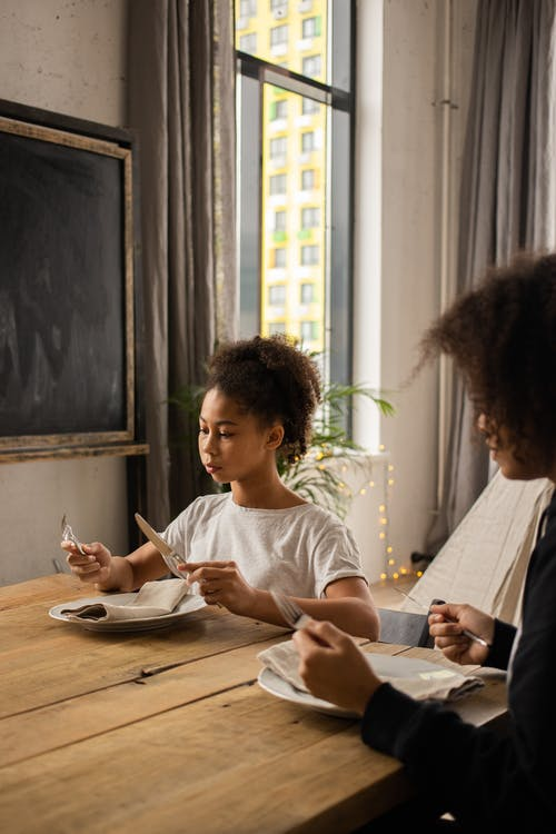 Serious African American girl with unrecognizable mother sitting at wooden table with plate and silverware in hands learning table manners