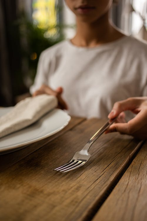 Crop unrecognizable female sitting at wooden table with white plate and fork while learning dining etiquette in room on blurred background