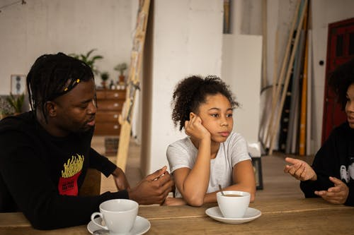 Frustrated black girl between arguing parents at table