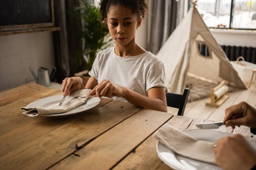 Pensive African American girl sitting at wooden table with plate and cutlery while looking at faceless person while learning dining etiquette