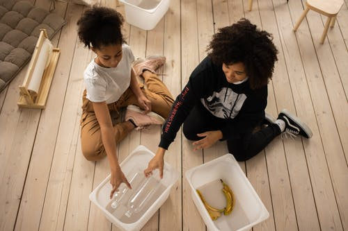 From above full body of African American mother and daughter sorting plastic bottles and banana peel into containers while sitting on wooden floor in room