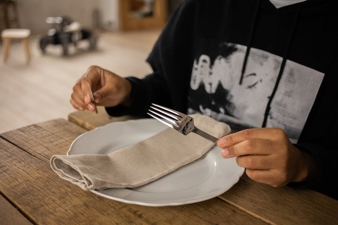 Crop anonymous person sitting at wooden table with fork and knife in hands near white plate with napkin on blurred background