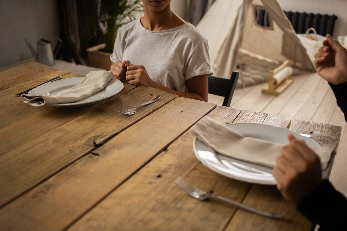 Crop faceless female sitting at wooden table with plate and cutlery near anonymous person while learning dining etiquette in light room