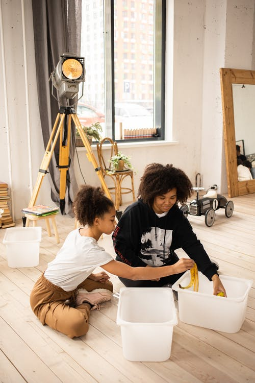 African American girls in casual clothes sitting on wooden floor while sorting banana peel into separate containers in light room