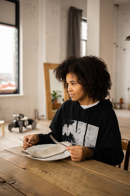 Black woman with plate at table