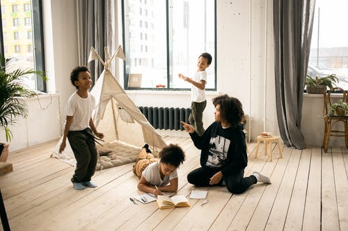 Full body of African American mother sitting on wooden floor near black kids playing in light room with blanket fort