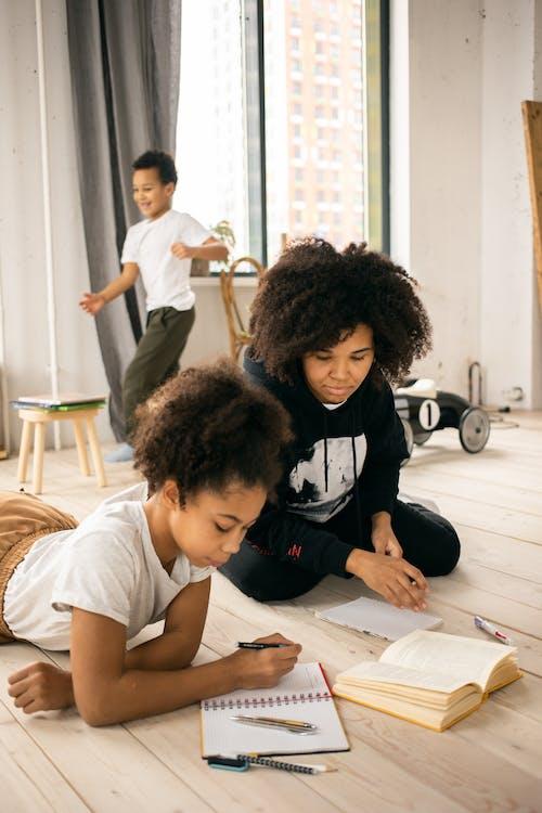 Focused black mother doing homework with daughter on floor