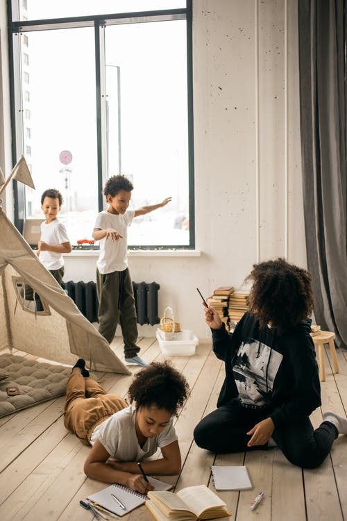 African American mother helping daughter with homework while sitting on wooden floor near sons playing in room near blanket fort