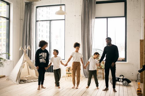 Full body of content African American parents with black kids standing together while spending time in light room with blanket fort