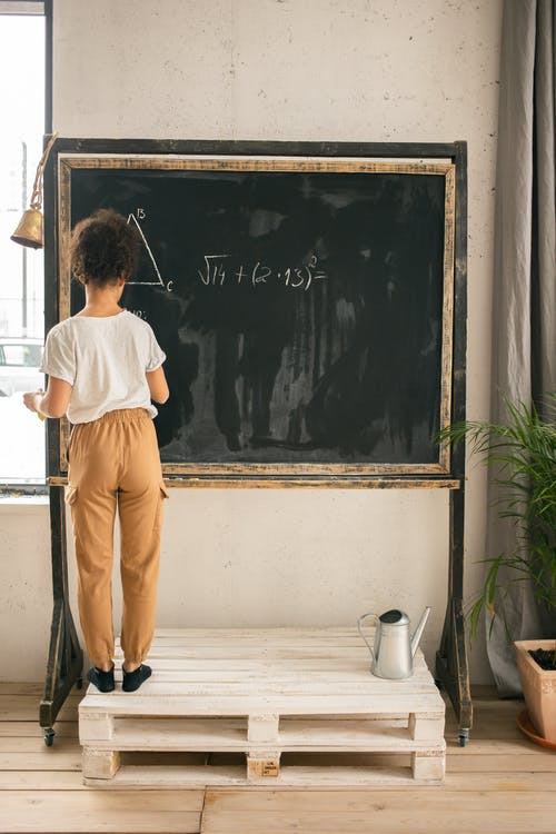 Back view full body of clever faceless girl writing on blackboard while solving mathematical equation during lesson in light room