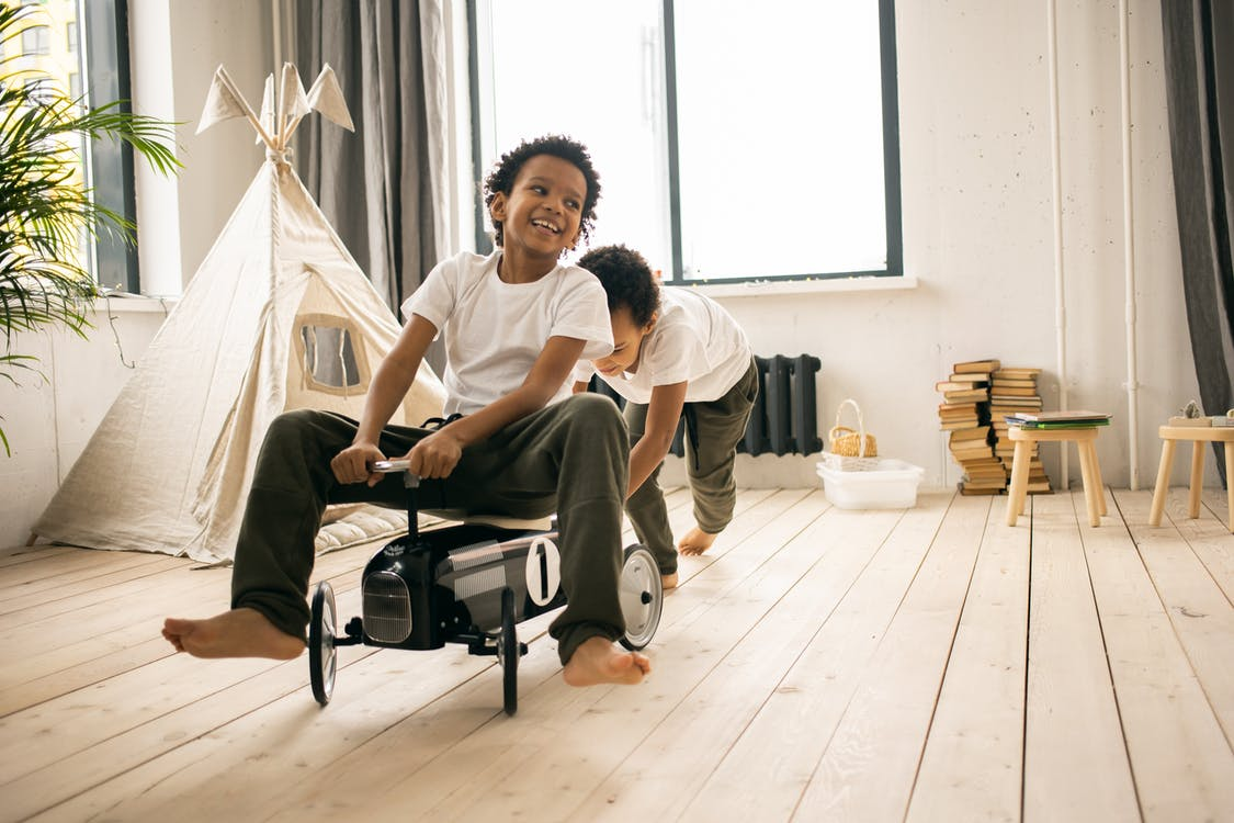 Happy barefoot African American brothers in casual wear riding toy car while playing together in light room with blanket fort