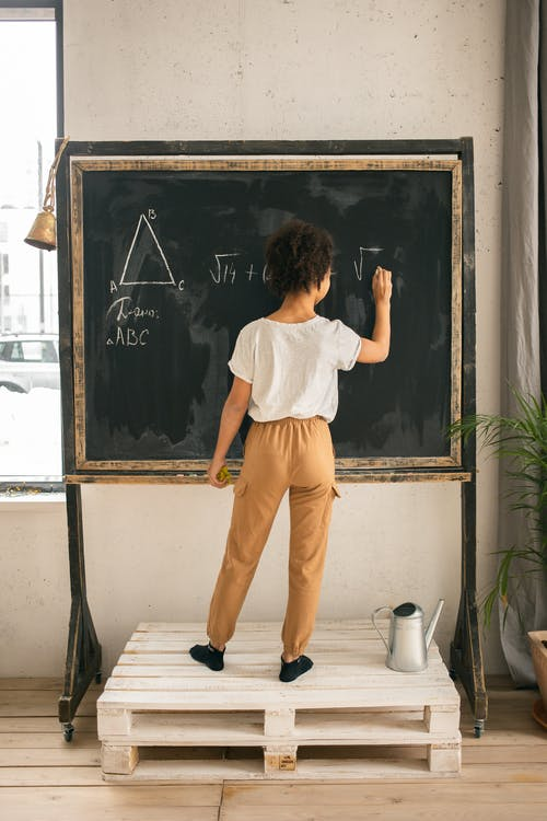 Full body back view of unrecognizable clever girl in casual clothes solving equation while writing on blackboard in light room