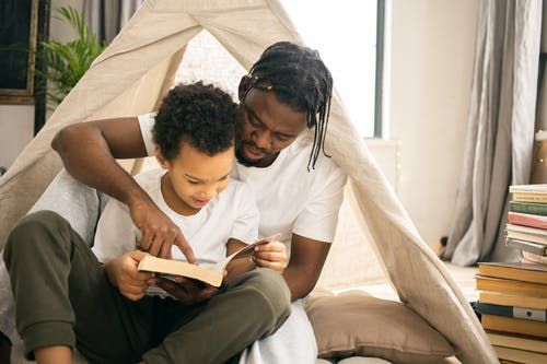 Focused African American dad sitting and reading book with positive sun un living room in daytime