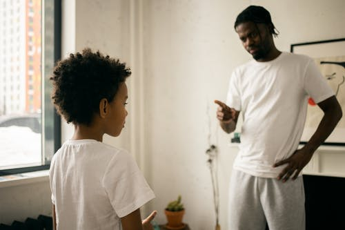 Young black father edifying calm son at home
