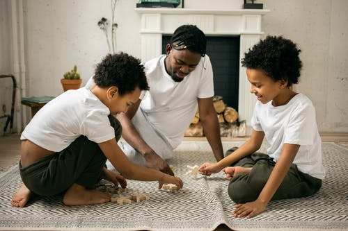 Happy young African American father in casual outfit smiling while sitting on floor and playing with wooden toys with positive twin sons during weekend at home