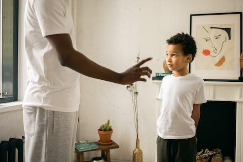 Crop unrecognizable black father disciplining adorable attentive son at home