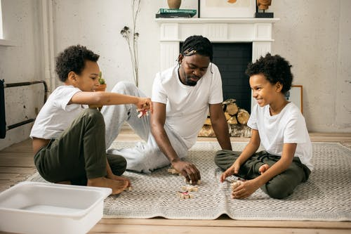 Full body of cheerful African American twin brothers in similar casual clothes smiling while sitting on floor and playing with toys together with happy young father