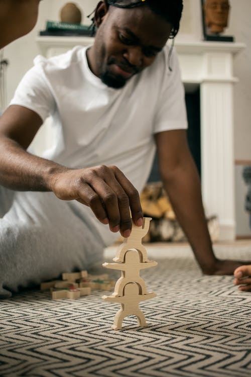 Delighted young black man stacking wooden figures on floor