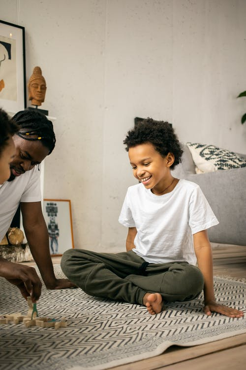 Happy black father and kids playing while spending time together at home