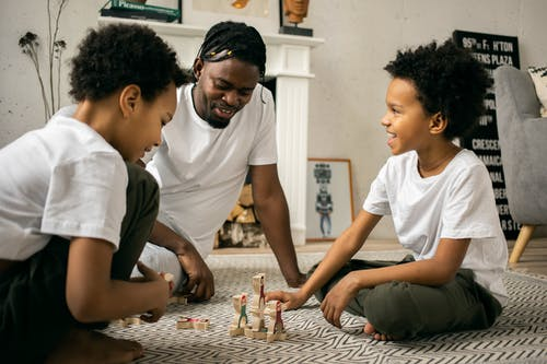 Black man playing with children in living room