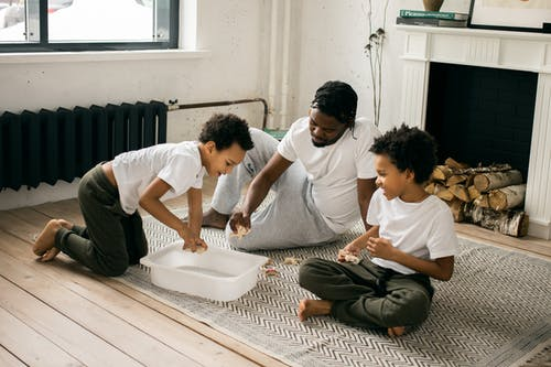 Calm African American father in casual clothes sitting on floor and playing with sons while spending time at home in daytime