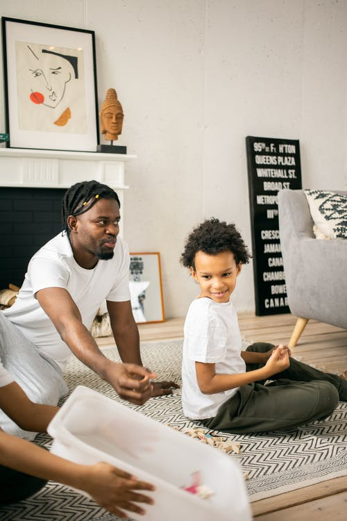 Black man playing with son in living room