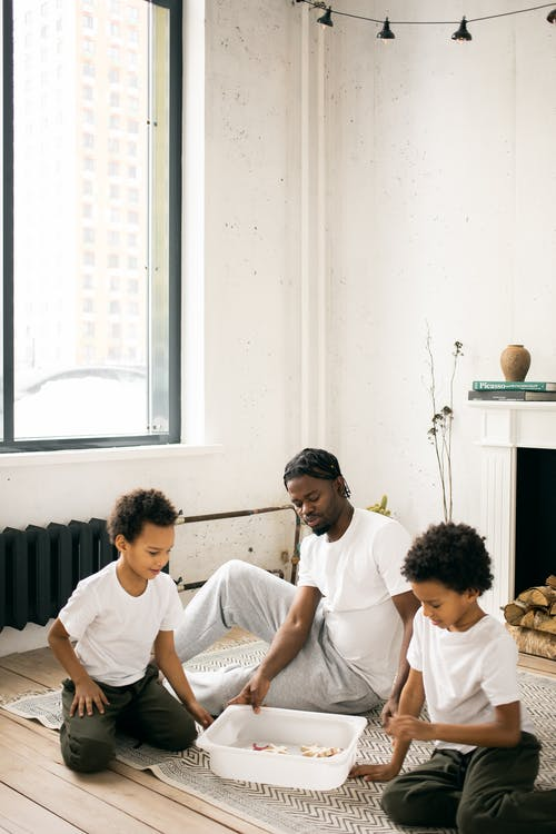 Calm African American father in casual clothes sitting on floor and playing with sons in light living room in daytime