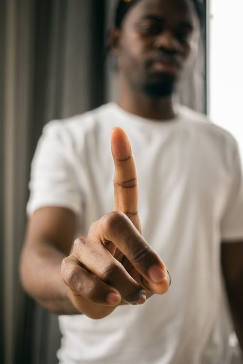 Black man with index finger pointing up