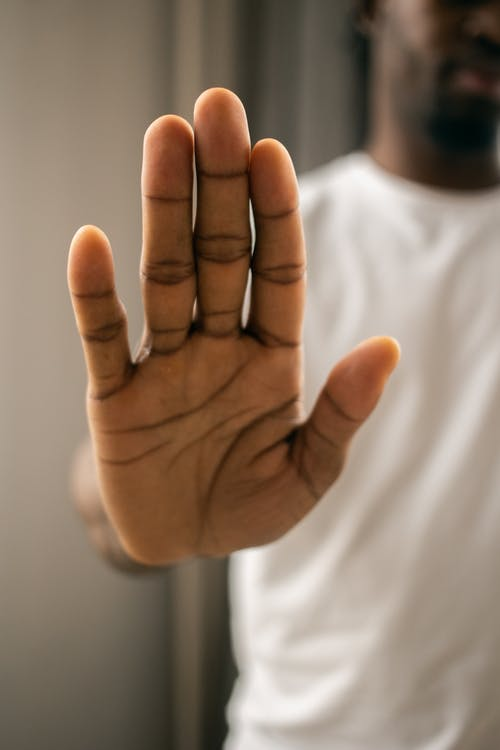 Faceless black man showing stop gesture with hand